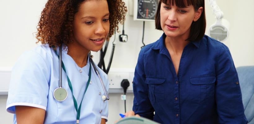 Female nurse talking to female patient