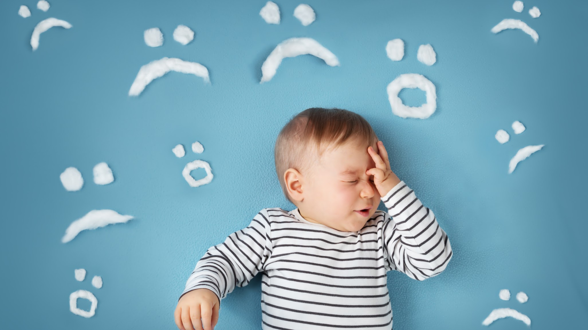 uhappy little boy on blue blanket background with sad smiley faces