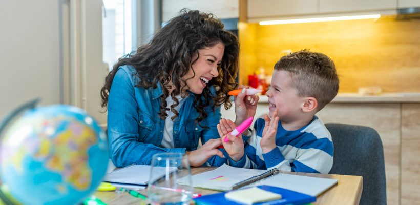 Mother helping with homework to her son indoor. Family, children and happy people concept. Mother and sons drawing together, mom helping with homework